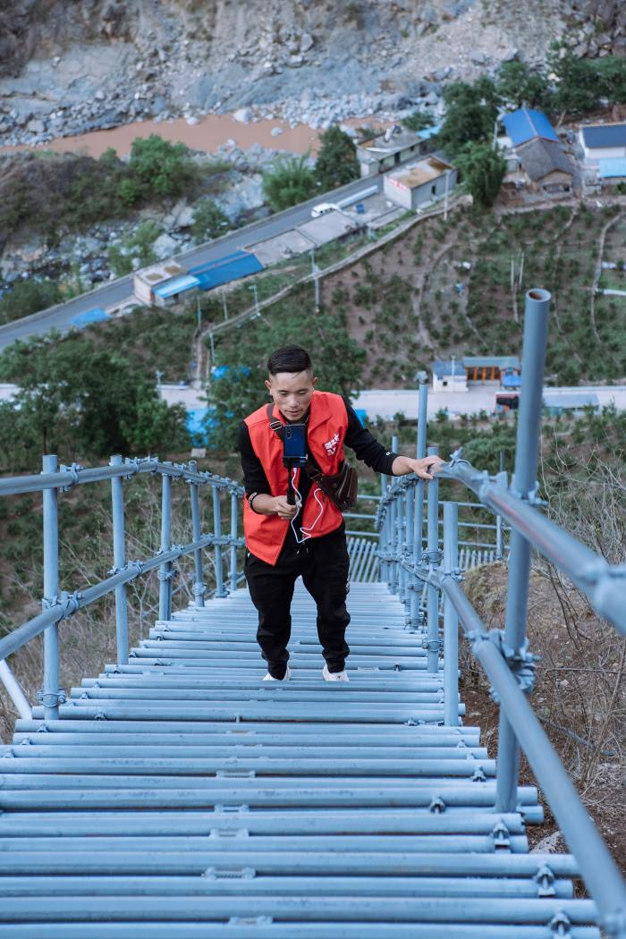 Jike Shibu live-streams the climb to his village on the new 800m steel ladder recently provided by local government