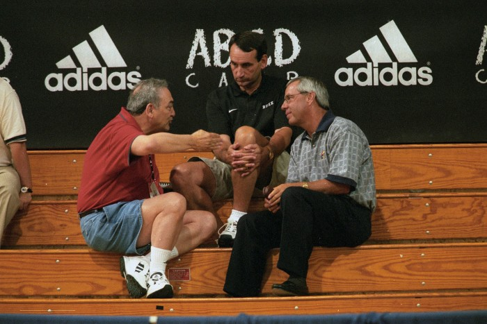 Adidas Scout Sonny Vaccaro (left) sits in the spectator stands with Kansas coach Roy Williams (right) and Duke coach Mike Krzyzewski (center) in 1998