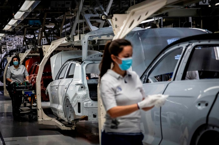 Employees work on the production line at a Volkswagen factory near Lisbon, Portugal. A recent VW advert showed one of its cars covered in a face mask, with the slogan 'Safety first' written underneath