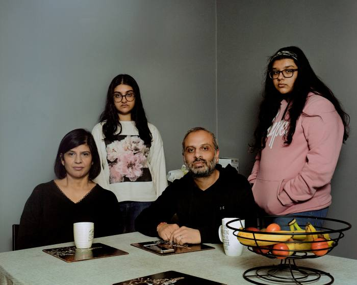 Devi and Manish Solanki (seated), with their daughters at home in East Ham. When Covid hit, Devi lost her sense of taste and smell; Manish ended up in ICU