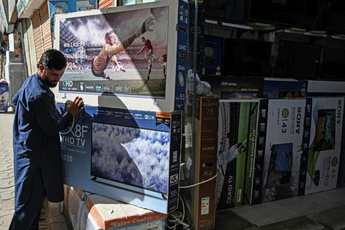 Un commerçant organise des boîtes de télévision dans un magasin de Kaboul