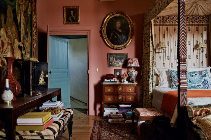 """In the master bedroom, aLa Carlière """"Belleme"""" cushion, £1,080, sits on the antique four-poster bed. Named after a local town, it uses a Lewis &Wood fabric, patched and over-embroidered with crewelwork. Thebedroom walls are painted Farrow & Ball Porphyry Pink"""