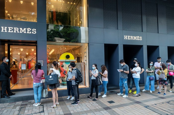Shoppers queue to enter an Hermès store in Hong Kong in August 2020