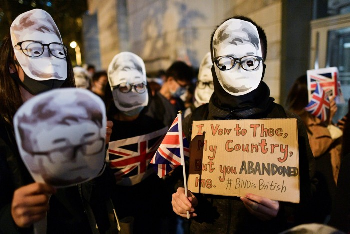 Masked protesters demonstrate in Hong Kong following the detention of former UK consulate worker Simon Cheng in 2019
