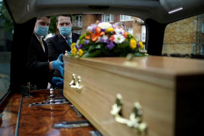 Guardian Funerals staff transport the casket of Covid-19 victim Dennis Clapham, 62, to Nab Wood Crematorium on Tuesday in Shipley, West Yorkshire