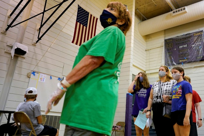Students and parents wear mask as they wait at a vaccination centre