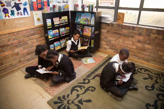 Students sitting on the floor reading independently or with a classmate