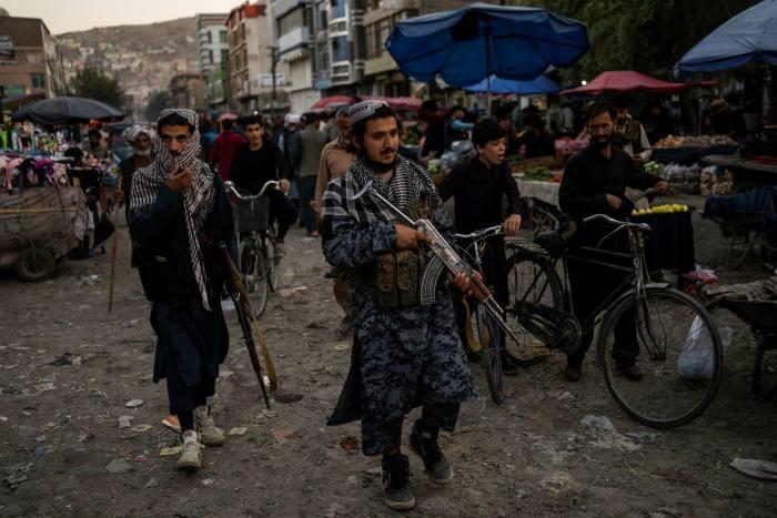 Taliban fighters patrol a market in Kabul