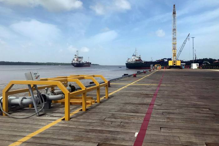 Vessels carry supplies for an offshore oil platform operated by ExxonMobil on the Demerara river, south of Georgetown, Guyana, wherethe companyrecently started production from deepwater oil blocks