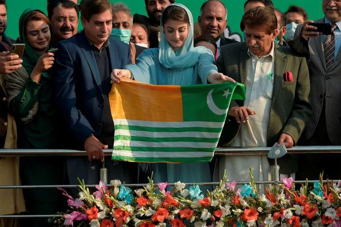 Maryam Nawaz (C), vice President Pakistan Muslim Leauge Nawaz (PML-N) and daughter of former premier Nawaz Sharif, holds a Pakistan-administered Kashmir flag during the PML-NFoundation Daycelebration in Islamabad on December 30, 2020