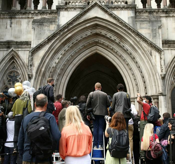 Reporters, photographers and fans wait outside the High Court in London on the final day of hearings in Johnny Depp's libel case against the Sun