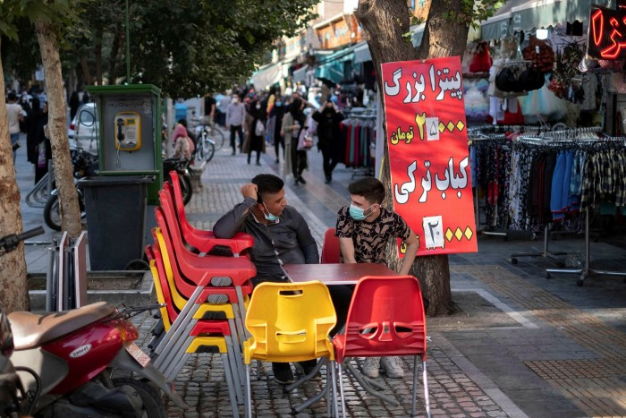 Iranians sit at a sidewalk cafe in northern Tehran