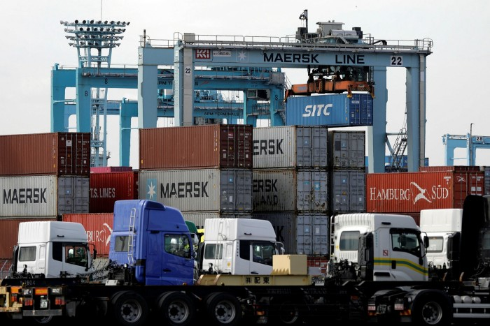 A crane moves a container while trucks wait to be loaded at a shipping terminal in Yokohama