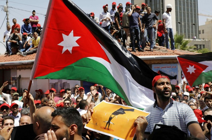 Jordanian protesters wave national flags in 2018. The 1989 IMF bailout, which required Jordan to cut its government spending, triggered protests in the tribal heartlands