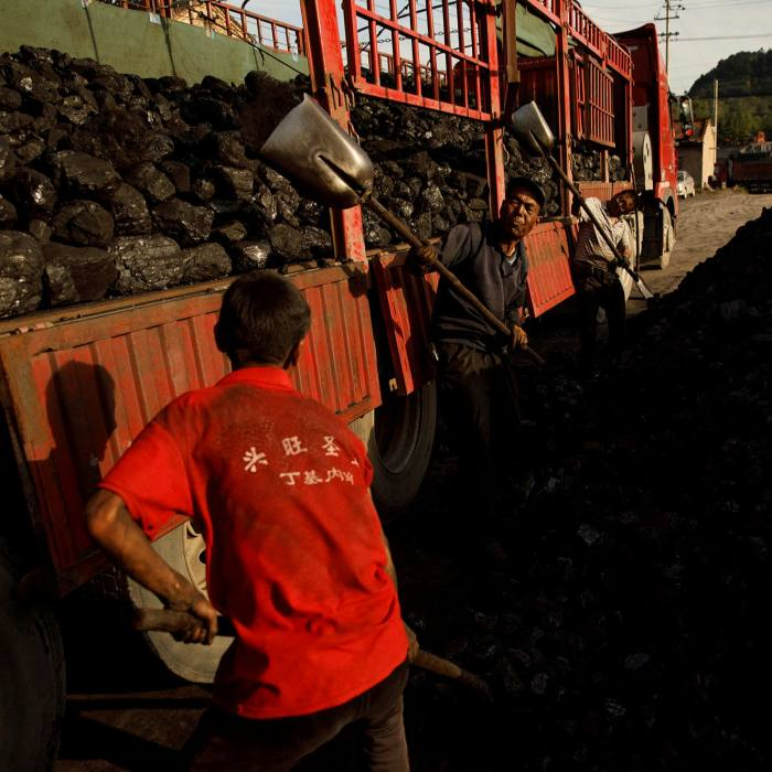 Workers shovel coal near a mine in Huating, Gansu province