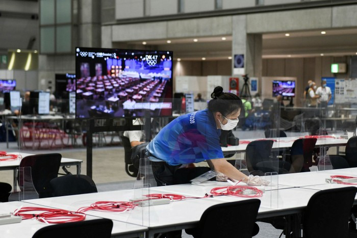 A worker cleans the tables in the press center for the Tokyo Games