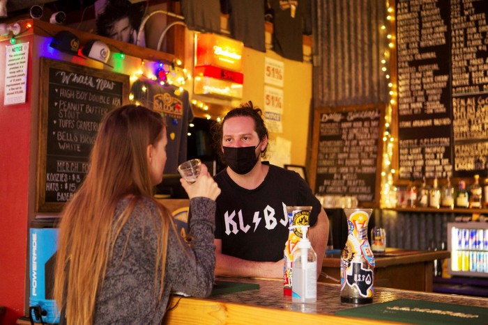 A bartender wears a mask as he talks to a customer at a tavern in Austin on Wednesday