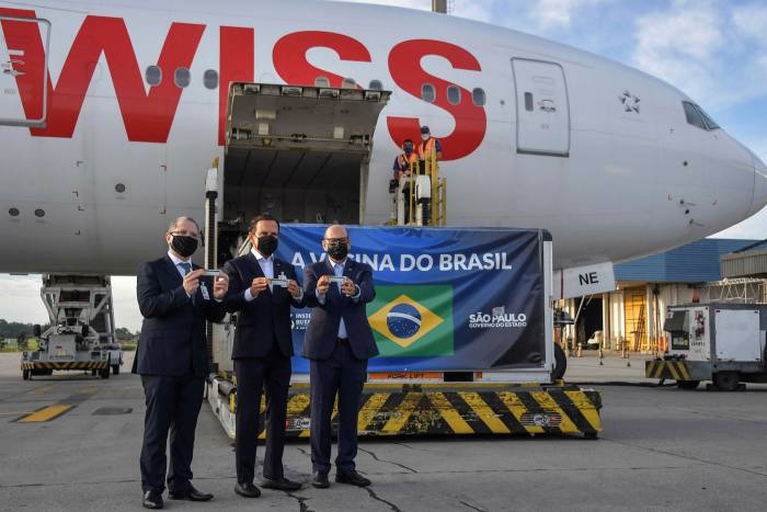 Brazilian officials at São Paulo airport next to a container carrying vaccines from China