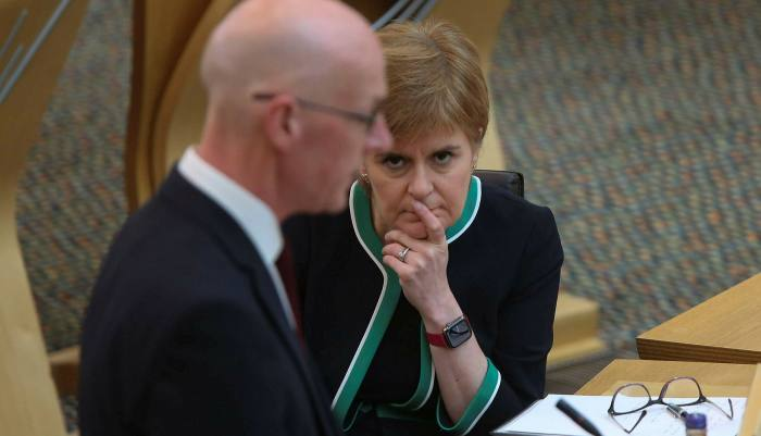 Scotland's first minister Nicola Sturgeon looks on as John Swinney, the education secretary, announces that 75,000 pupils will have their qualifications upgraded after public outcry over the original results Fraser Bremner/Scottish Daily Mail/PA