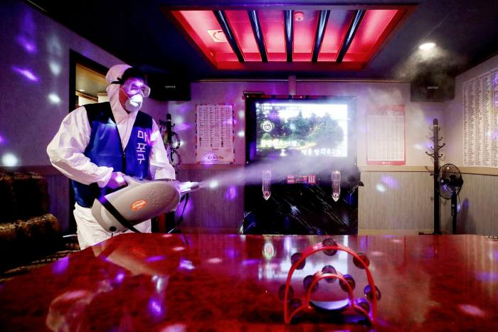 A worker disinfects a Karaoke room in Seoul. Anyone entering one of about 80,000 entertainment venuesacross the countryhas to register via a QR code,making it easier for officials to trace Covid-19 outbreaks