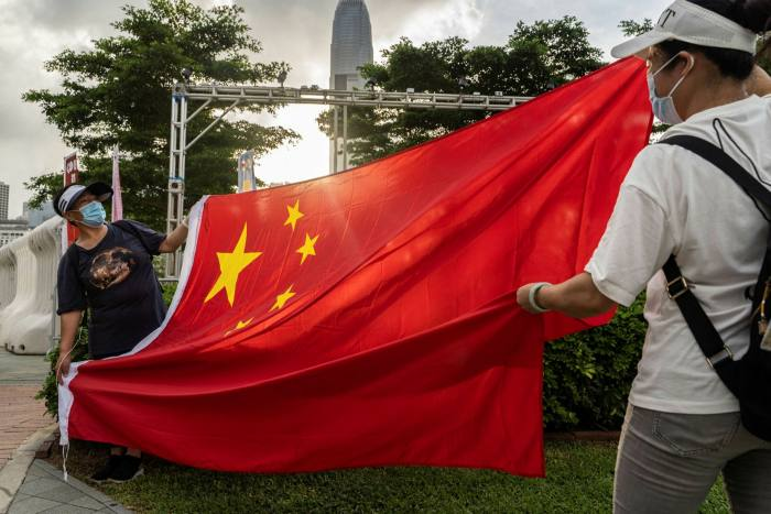 A Chinese flag is hoisted in front of a light show celebrating the centenary of the Chinese Community Party and the anniversary of Hong Kong's return to Chinese rule on July 1 in Tamar Park, Hong Kong.
