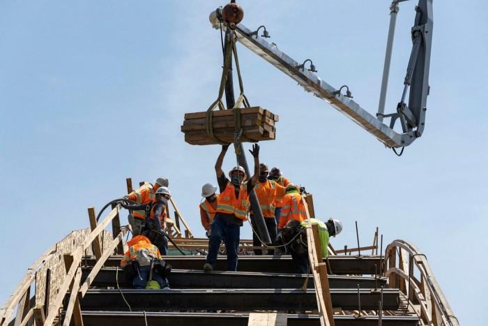 'N Skanska AB -konstruksiewerker lei 'n hyskraan wat hout dra terwyl 'n betonboom beton stort op die vervangingsprojek van die Sixth Street Viaduct in Los Angeles, Kalifornië
