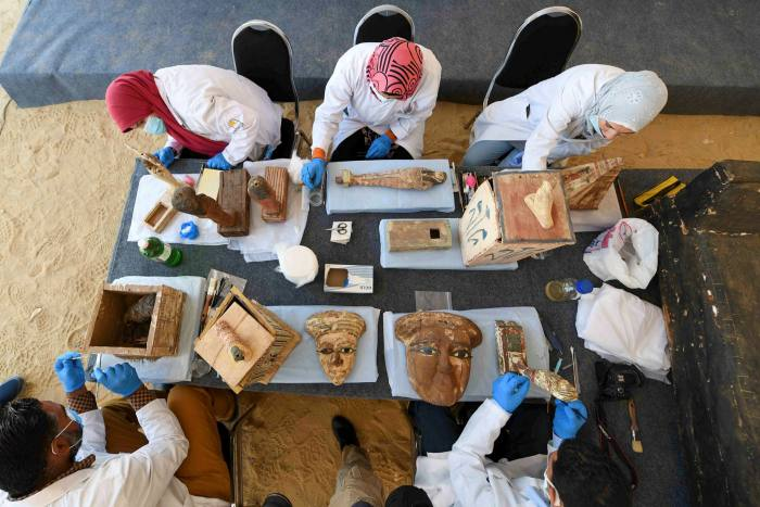 Archaeologists clean up statues and funeral masks found in Saqqara