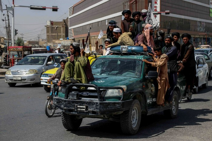 Taliban fighters drive through Kandahar on Tuesday as they celebrate the withdrawal of US forces
