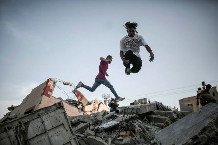 Palestinian youths practise parkour between houses destroyed by Israeli attacks in Gaza