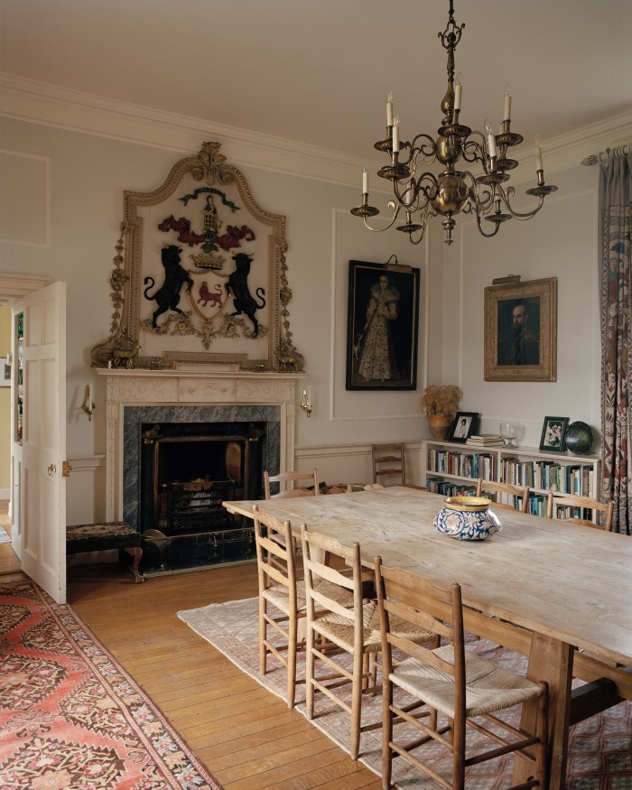 The Hall is used as the family dining room, with anoak table by Arts and Crafts architect Philip Webb. The Ogilvy coat of arms is set inrelief above the fireplace