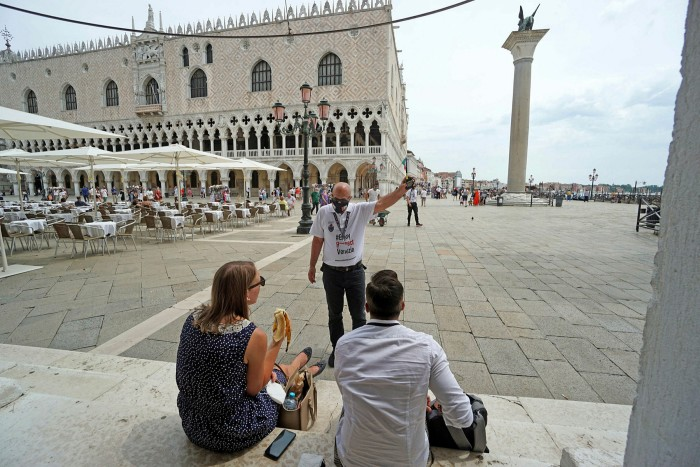 One of the operators in charge of monitoring tourist behavior talks to a couple in Venice