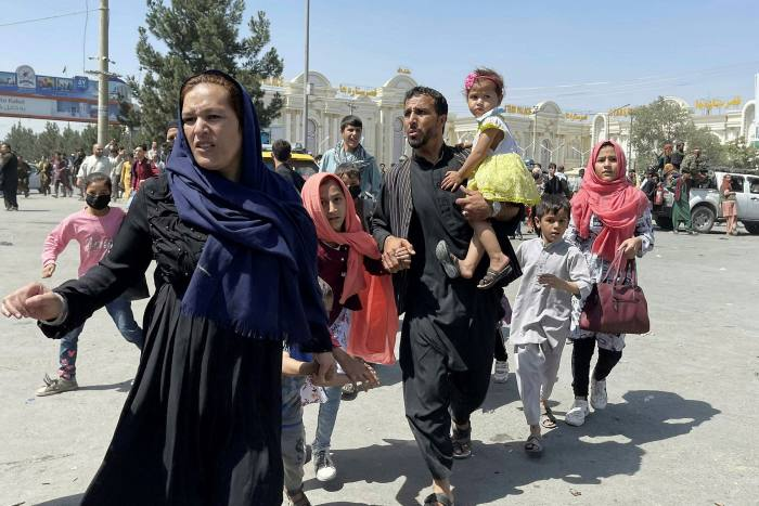 An Afghan family rushes to the international airport as they flee Kabul last week