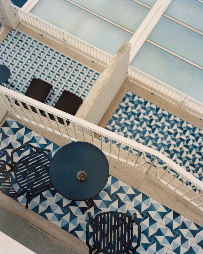 A cascade of balconies, each with a unique pattern of tiles that is echoed inside the room