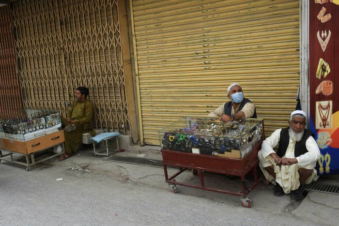 Vendors selling watches sit beside a closed market after a  lockdown was imposed in Quetta, northern Balochistan