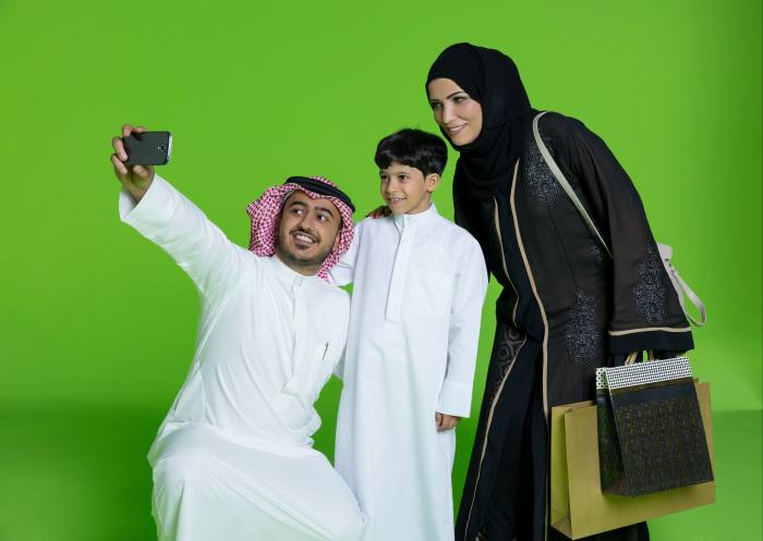 A man holding up the camera to take a photo of himself, a young boy and a woman