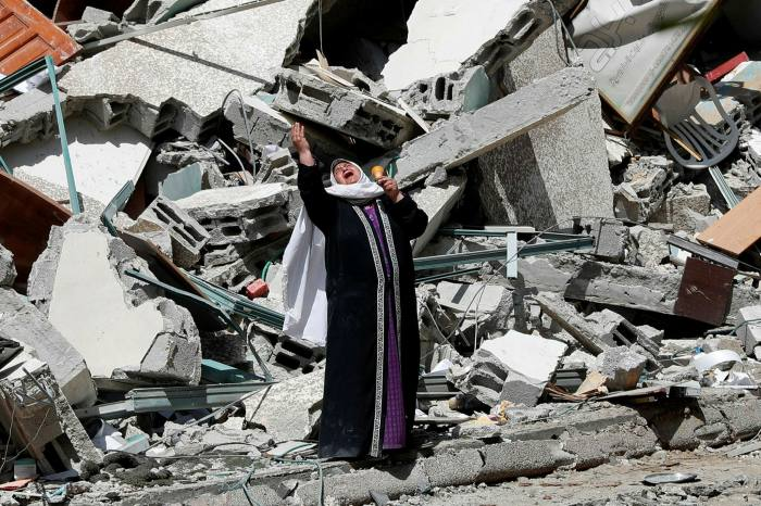 A woman stands near the rubble of a dilapidated building in Gaza City on Sunday
