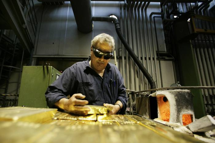 An employee holds a 12.5kg gold bar at a plant of Argor-Heraeus SA, gold refiner and bar manufacturer, in Mendrisio, Switzerland