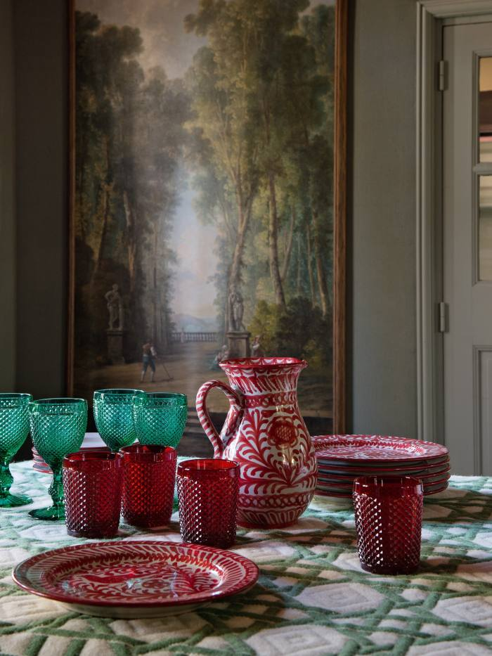In Pierre Sauvage's Normandy home, Casa Lopez dishes sit on a jacquard rug that serves as a tablecloth