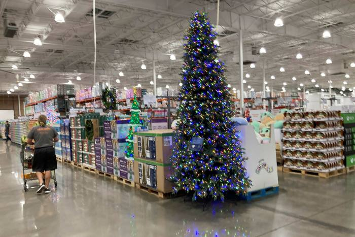 A lone shopper pushes a cart past a display for Christmas sales in a Costco warehouse