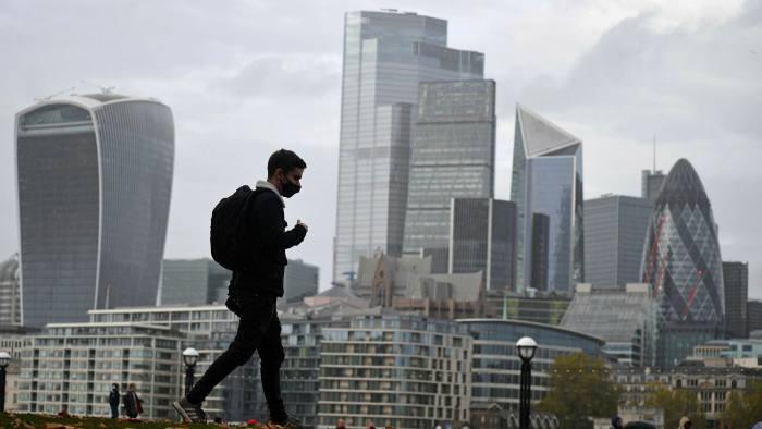 Domingo por la mañana bajando: un viajero enmascarado camina a lo largo del río Támesis en Londres antes del renovado cierre de noviembre