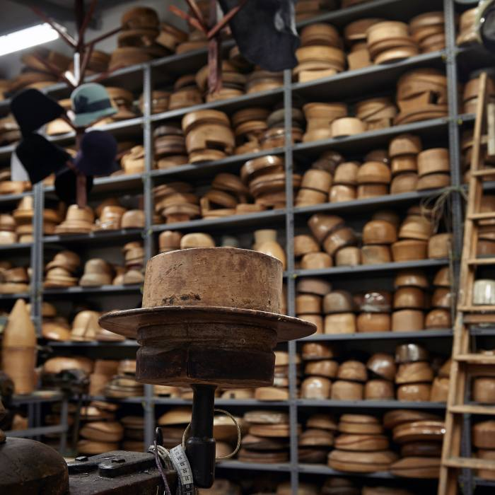 The milliner's workshop is lined with antique walnut hat blocks