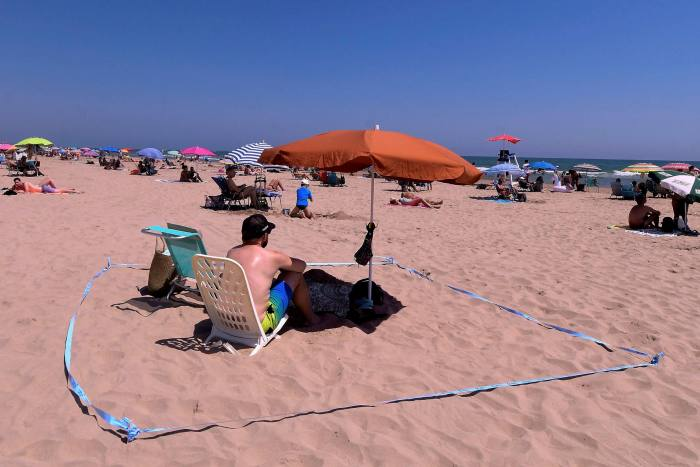 A man creates social distance using tape at the Nord Beach in Gandia, near Valencia. More than 40,000 excess deaths have been recorded since Spain was hit by coronavirus