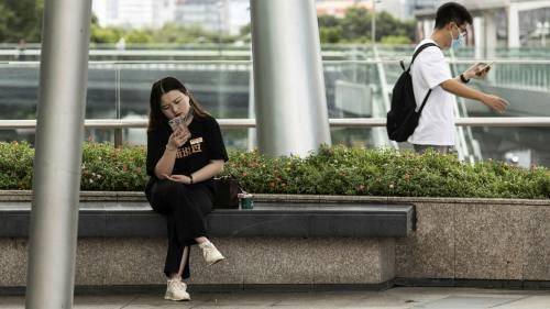 People look at their mobile phones in Shanghai