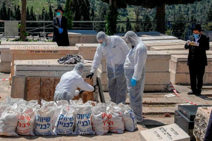 Ultraorthodox Jews wearing masks watch as funeral workers prepare the body of former Sephardic chief rabbi of Israel Eliahu Bakshi-Doron