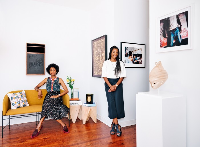Naomi Beckwith (left) and Catherine Sarr at Sarr's house in Chicago. On walls from far left, Nate Young's Votive Deposit, 2019, Lina Iris Viktor's Constellation VI, 2018, Lorraine O'Grady's Art is... (Cop Eyeing Young Man), 1983/2009, and Mimi Cherono Ng'ok's Untitled, 1983/2009. On plinth: Kifouli Dossou's Guélédé Mask Untitled, 2014