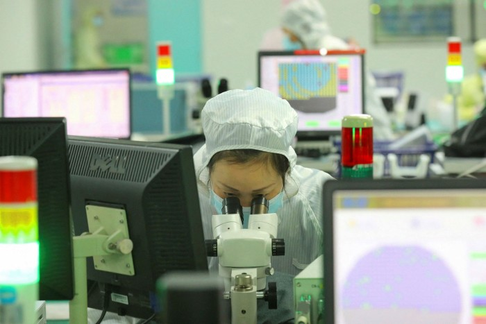 A lab worker makes chips at a factory Jiangsu province, China. The Biden administration has tried to address some of the current supply chain disruption, particularly in the semiconductor sector, that has driven up the cost of cars and other goods