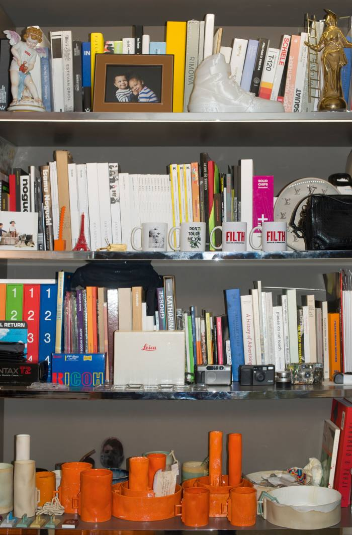 Virgil Abloh's shelves make for an impressive CV. Each one boasts of his multi-disciplinary career interests, with references to Louis Vuitton, where he is artistic director of menswear, as well as nods to his own Off-White label. But he punctuates them with personal details designed to curtail any hubris: note the particular interest in pocket-sized cameras, family photos and kitsch religious curios