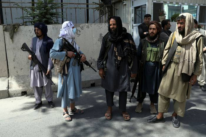 Taliban fighters stand guard at the main gate leading to the presidential palace on August 16
