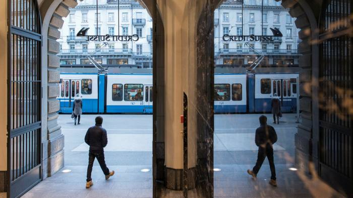 People walk in the front of the Credit Suisse bank at the tram stop Paradeplatz in the square's center in Zurich