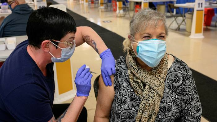 A healthcare worker administers a Covid vaccine to a woman in West Virginia